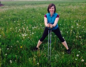 Frau in Trainingskelidung und Nordicwalkingstöcken steht in der Krätsche auf einer Wiese