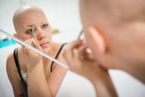 Frau ohne Haare beim Schminken