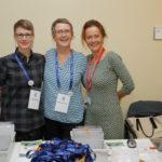 Drei Frauen stehen eng beisammen und lachen