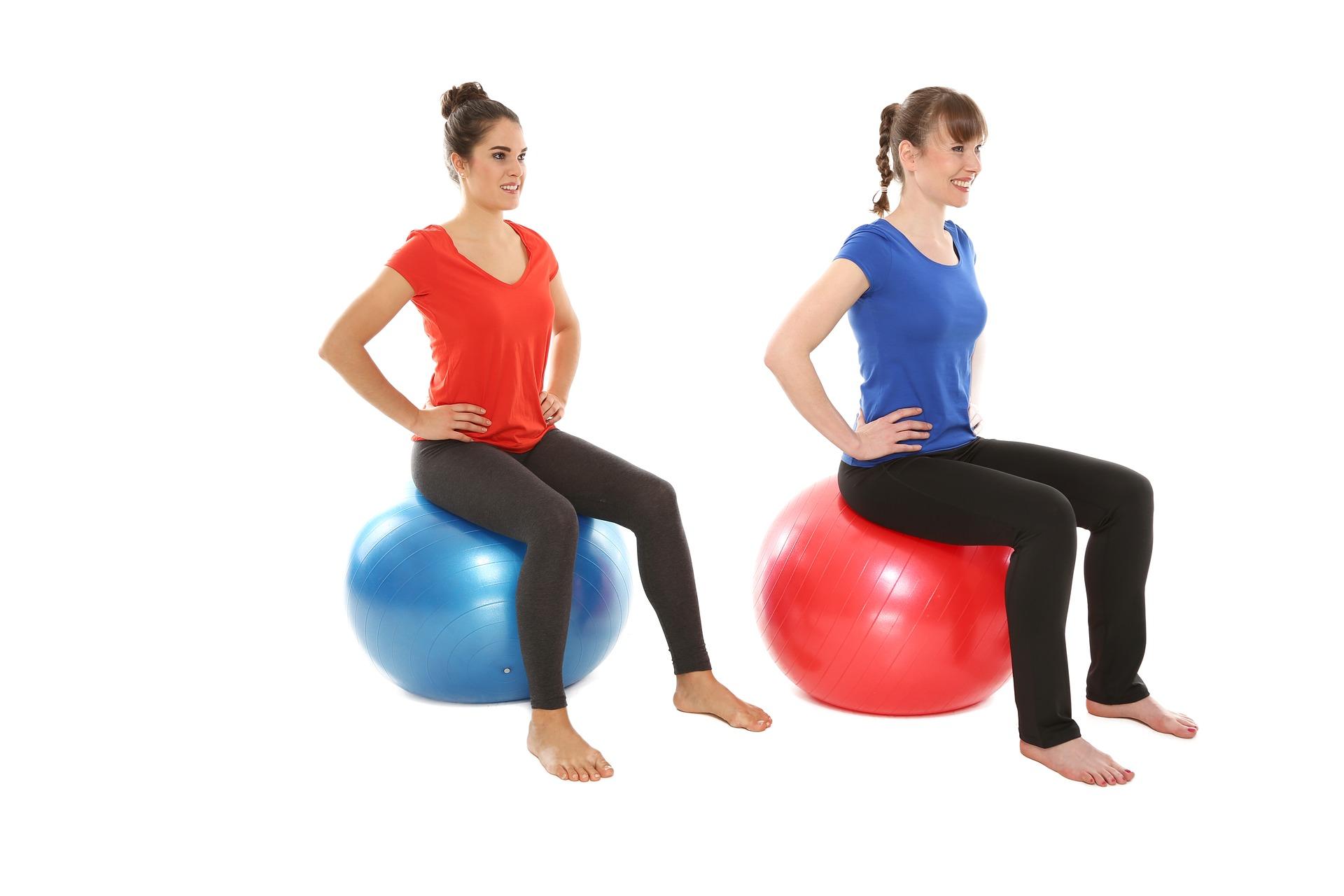 zwei junge frauen machen gymnastik auf einem Ball